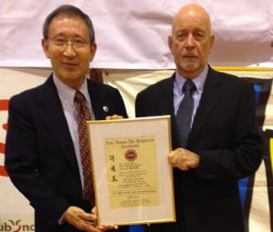 BTC Chairman Dave Oliver receiving his promotion certificate to promote him to 9th Dan Grand Master from Grandmaster C.K. Choi, 9th Dan. The award was made by: Grandmaster CK Choi, Grandmaster J. C. Kim, Grandmaster Sang Min Cho and Grandmaster Woo Yup Yang, all original tae kwon do pioneers.